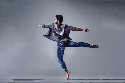 Man-wearing-blue-jeans-doing-pirouette-spin-1701202